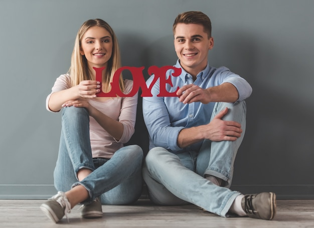 Young couple is holding a word love