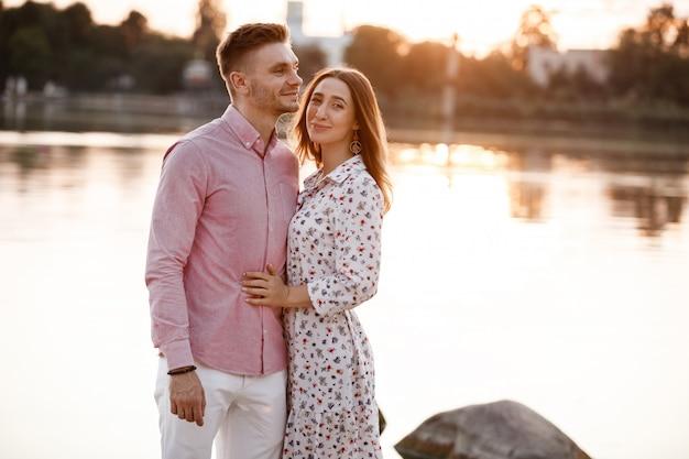 若いカップルは抱き合って、湖の近くの夕暮れ時に歩きます。男と女の夏休み。素敵な家族の概念。セレクティブフォーカス