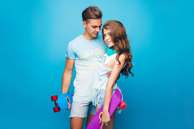 Young couple is hugging on blue background in studio. they wear t-shirts, jeans shorts, hold skateboards.