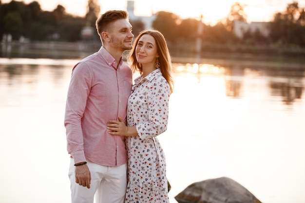 Young couple is hugging and walking at sunset near the lake. man and woman on summer holiday. concept of lovely family. selective focus