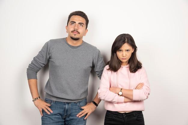 Молодая пара злится друг на друга, стоя на белом.
