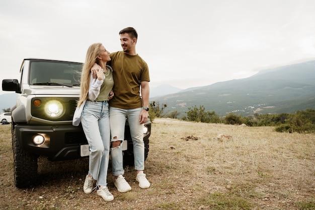 若いカップルは車で山へのロマンチックな旅行にあります