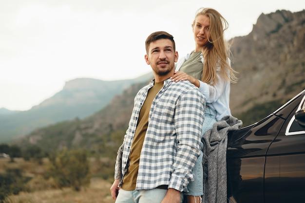 Молодая пара в романтическом путешествии в горы на машине