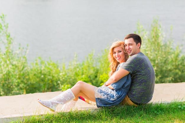 若いカップルは湖の公園でロマンチックです。緑の芝生で夏の太陽の下で男と女が座っています。