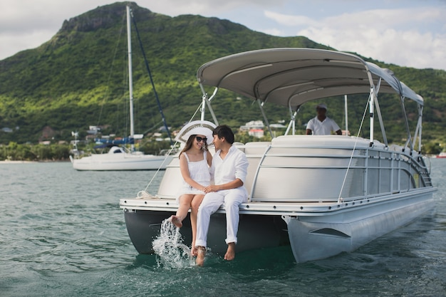 Young couple is sailing on a yacht in the indian ocean. man and woman sit on the edge of the yacht