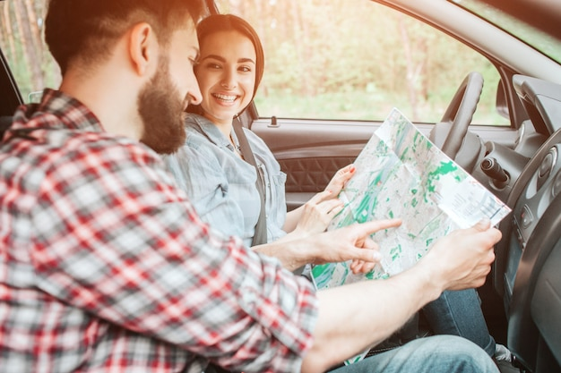 Young couple is sitting in car. they are holding a big map with their hands. guy is pointing on map. girl is looking at him and smiling.