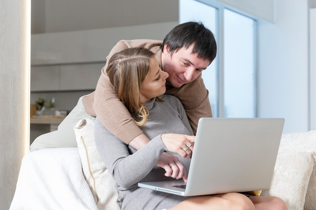 A young couple is sitting on the couch and shopping online
