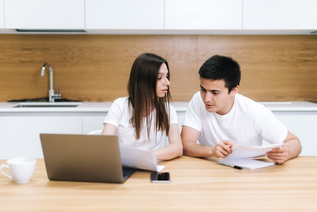 Young couple is sitting at kitchen table, use laptop and taking care of utility bills and house maintenance documents. wife and husband read paperwork, pay bank credit online via internet