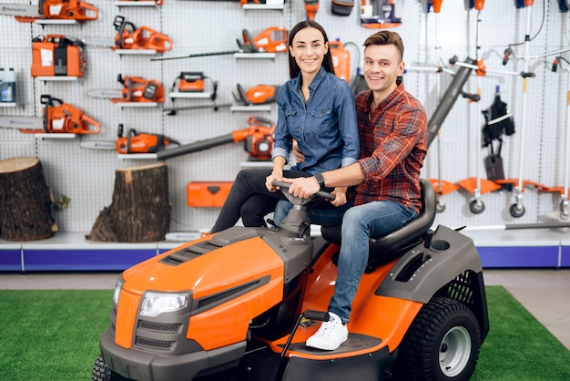 A young couple is sitting on a lawn mower.