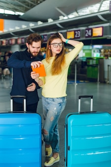 Young couple is standing in airport with two suitcases near. she has long hair, sweater, jeans, and tablet in hand. he wears beard, black shirt and pants. they look a little bit upset, maybe lost.