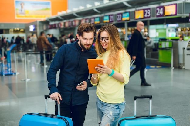 若いカップルは空港で2つのスーツケースの間に立っています。彼女は長い髪、メガネ、セーター、ジーンズを持っています。彼はあごひげとズボンが付いた黒いシャツを着ています。彼らはタブレットで読んでいます。