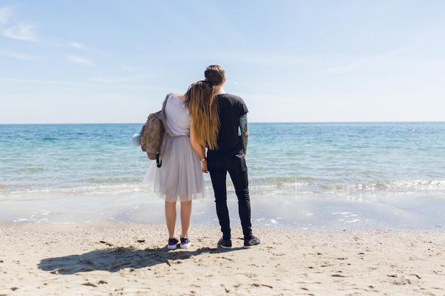 Young couple is standing near sea