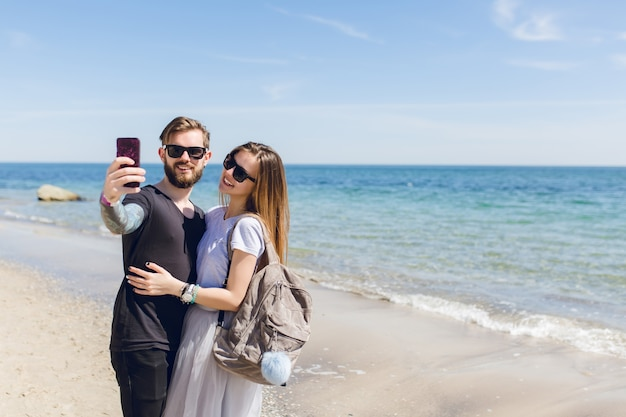 Young couple is taking a selfie photo near sea.