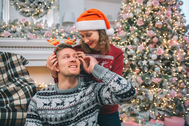 Young couple is together. woman stands behind man and keeps hands on her head. he looks at her and touches her hand. they are in decorated room near fireplace and christmas tree.