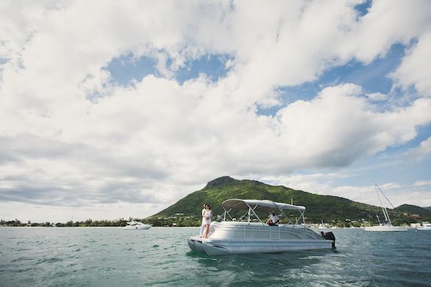 Молодая пара путешествует на яхте в индийском океане. на носу лодки обнимает любящая семья