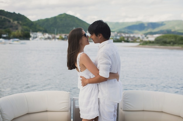 Young couple is traveling on a yacht in the indian ocean. man and a woman stand on the edge of the boat and kiss