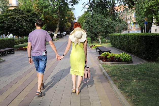 Молодая пара гуляет по пустынной аллее в солнечный летний день