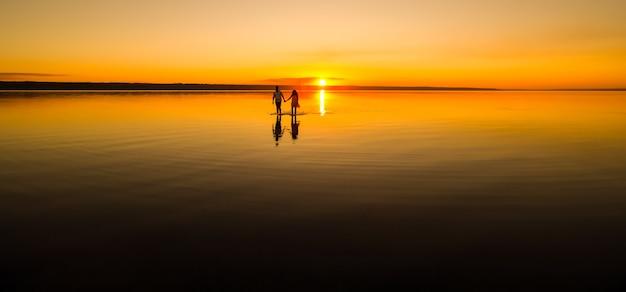 若いカップルが夏のビーチの水の中を歩いています。海に沈む夕日。太陽を背景にした2つのシルエット。ロマンチックなラブストーリーでちょうど夫婦。休日の新婚旅行の男女。