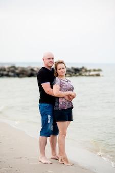 젊은 부부는 바다에서 걷고있다