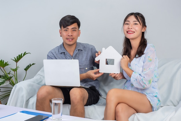 Young couple is working from home while young girl is holding paper house on sofa.