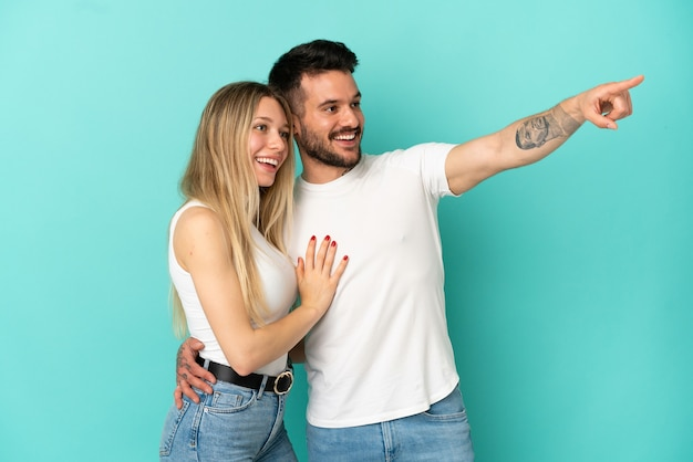 Young couple over isolated blue background pointing finger to the side and presenting a product