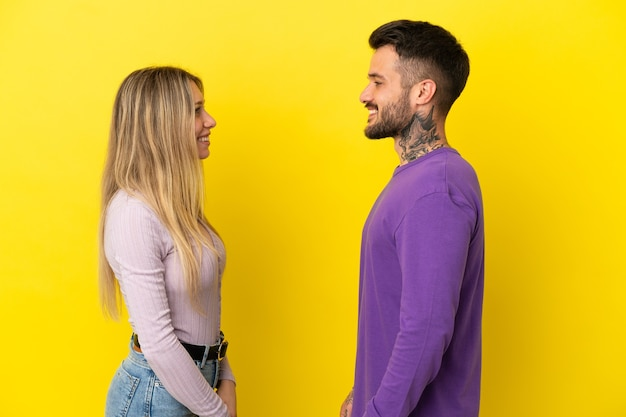 Young couple over isolated yellow background looking at each other