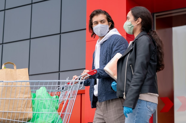 Young couple in jackets and cloth mask leaving supermarket together after shopping, man pushing cart