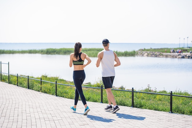 Young couple jogging by lake