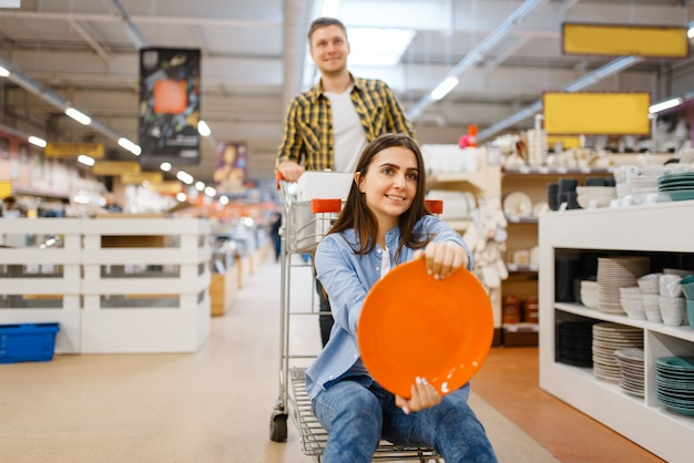 Young couple jokes with cart and plate in houseware store. man and woman buying home goods in market, family in kitchenware supply shop