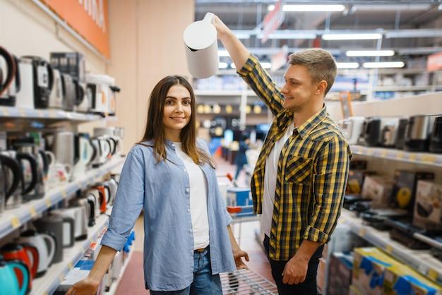 젊은 부부는 전자 제품 매장에서 전기 주전자와 농담. 남자와 여자는 시장에서 가전 제품을 구입