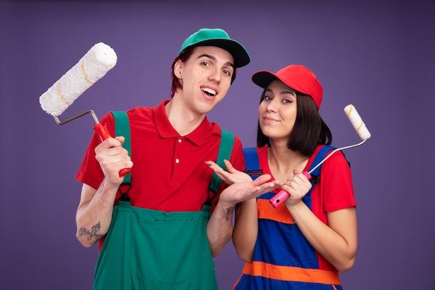 Coppia giovane ragazzo gioioso e ragazza compiaciuta in uniforme da operaio edile e cappuccio che tiene il rullo di vernice che mostra la mano vuota