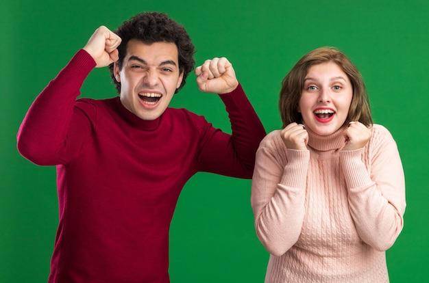 若いカップルのうれしそうな男は、バレンタインデーに女性を興奮させ、緑の壁に隔離されたイエスのジェスチャーをしている正面を見て