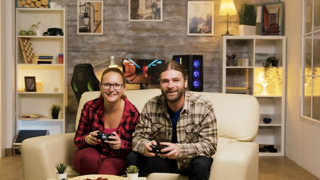 Young couple jumping up from the couch celebrating their victory while playing video games using wireless controllers.