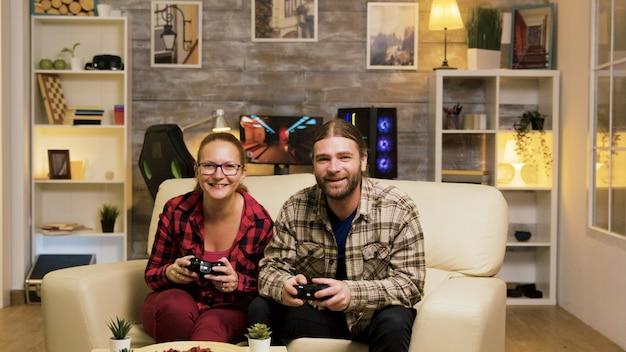 ワイヤレスコントローラーを使用してビデオゲームをプレイしながら、勝利を祝うソファから飛び上がる若いカップル。