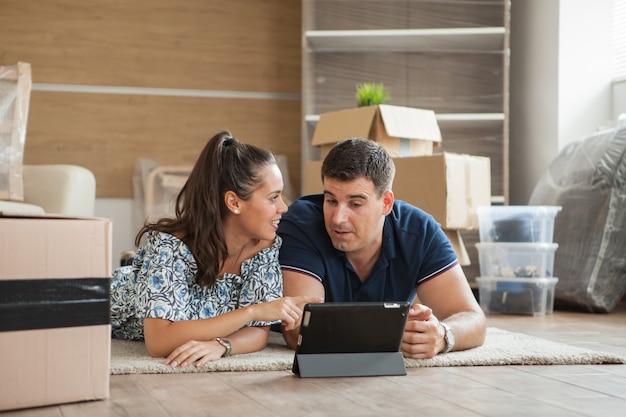 若いカップルが新しいアパートに引っ越してきて、タブレットを手にした家具をオンラインで買い物しています
