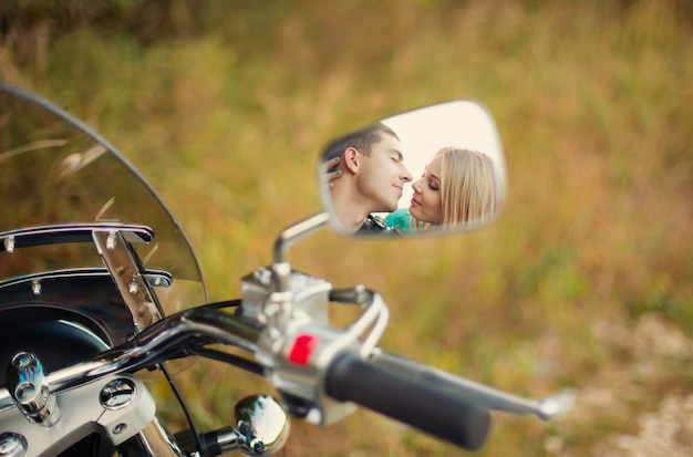 Young couple kiss in mirror on beautiful motorcycle on road.
