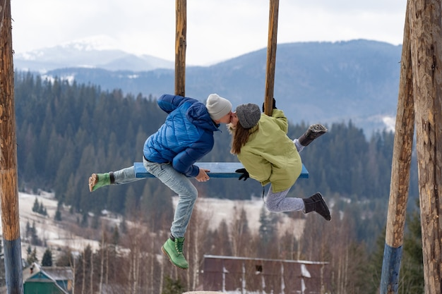 A young couple kiss on a swing in the winter mountains. relationship, love, togetherness concept.