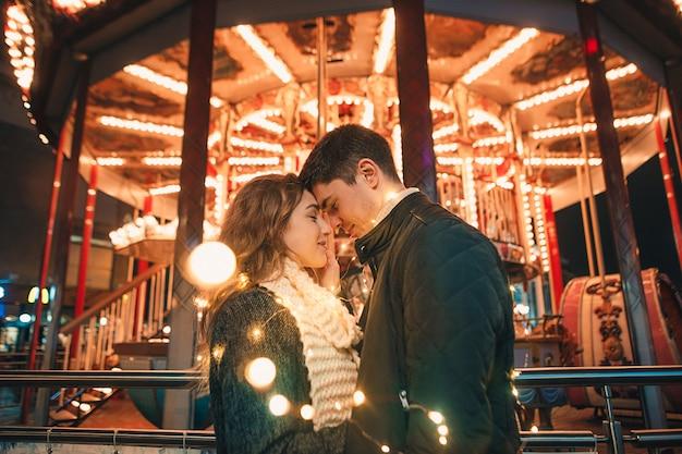 Молодая пара целуется и обнимается на улице на ночной улице во время рождества