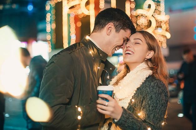 若いカップルがキスをし、クリスマスの時に夜の街で屋外を抱いて