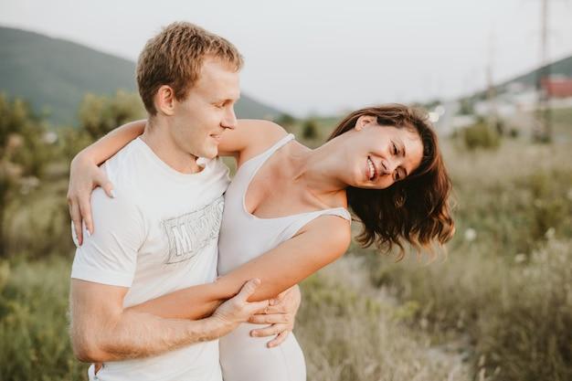 若いカップルが夏に屋外でキスをし、抱きしめます。