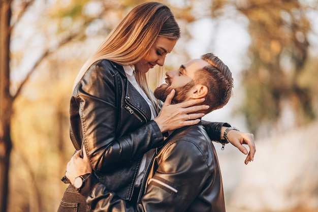 Young couple kissing in autumnal park. a man raised his woman in his arms