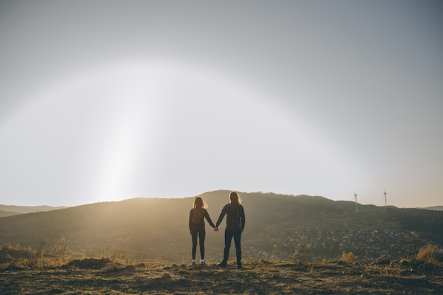 Young couple kissing on the background of a sunset in the field.