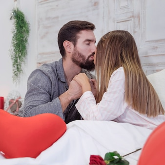 Young couple kissing on bed