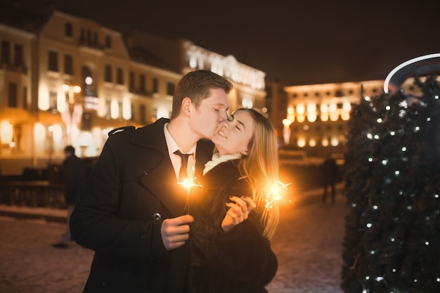 Young couple kissing in city with bokeh background. st. valentine's day concept