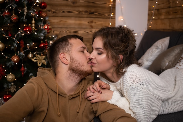 Young couple kissing at home at christmas time near beautifully decorated christmas tree