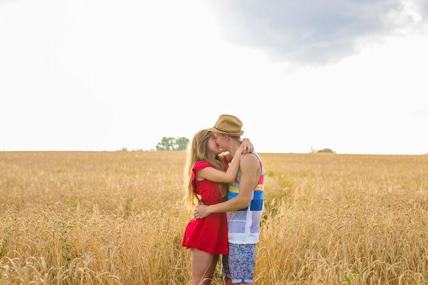 필드에서 키스하는 젊은 부부. 밀밭의 중간에 백인 남자를 포옹하고 서로 키스하는 젊은 여자. 열정과 사랑에 대한 개념
