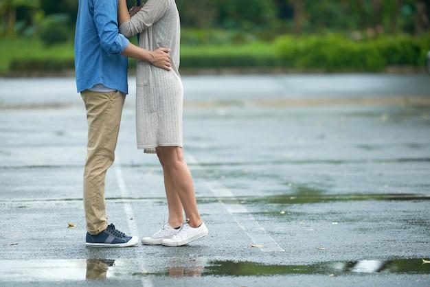 若いカップルが雨の中でキス