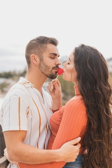 Young couple kissing lollipop