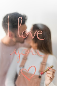 Young couple kissing near i love you inscription on glass