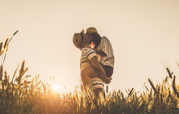 若いカップルが麦畑の夕日にキス